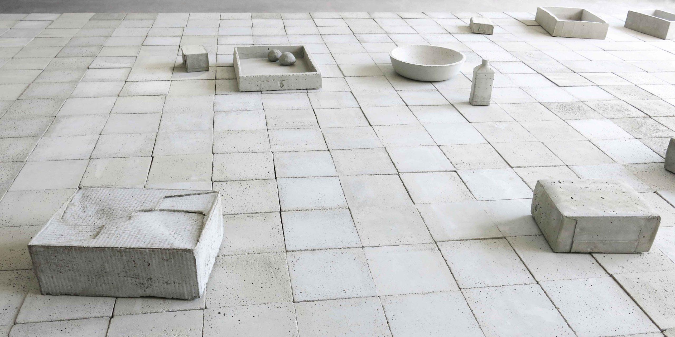 Pavimento in piastrelle di cemento con oggetti in cemento di Cristina Treppo