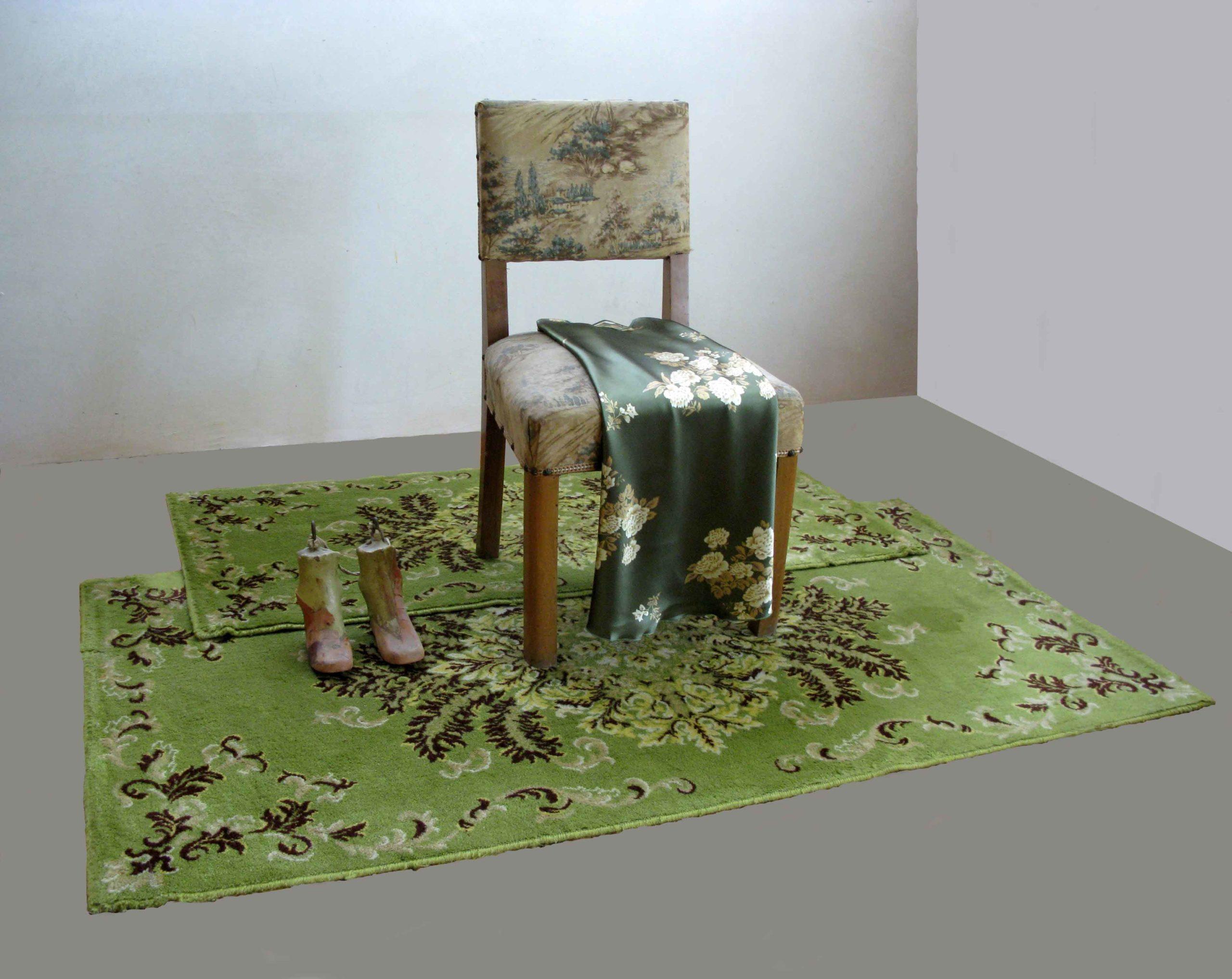 Composizione di Cristina Treppo con tappeti, sedia, vestito e calchi ortopedici