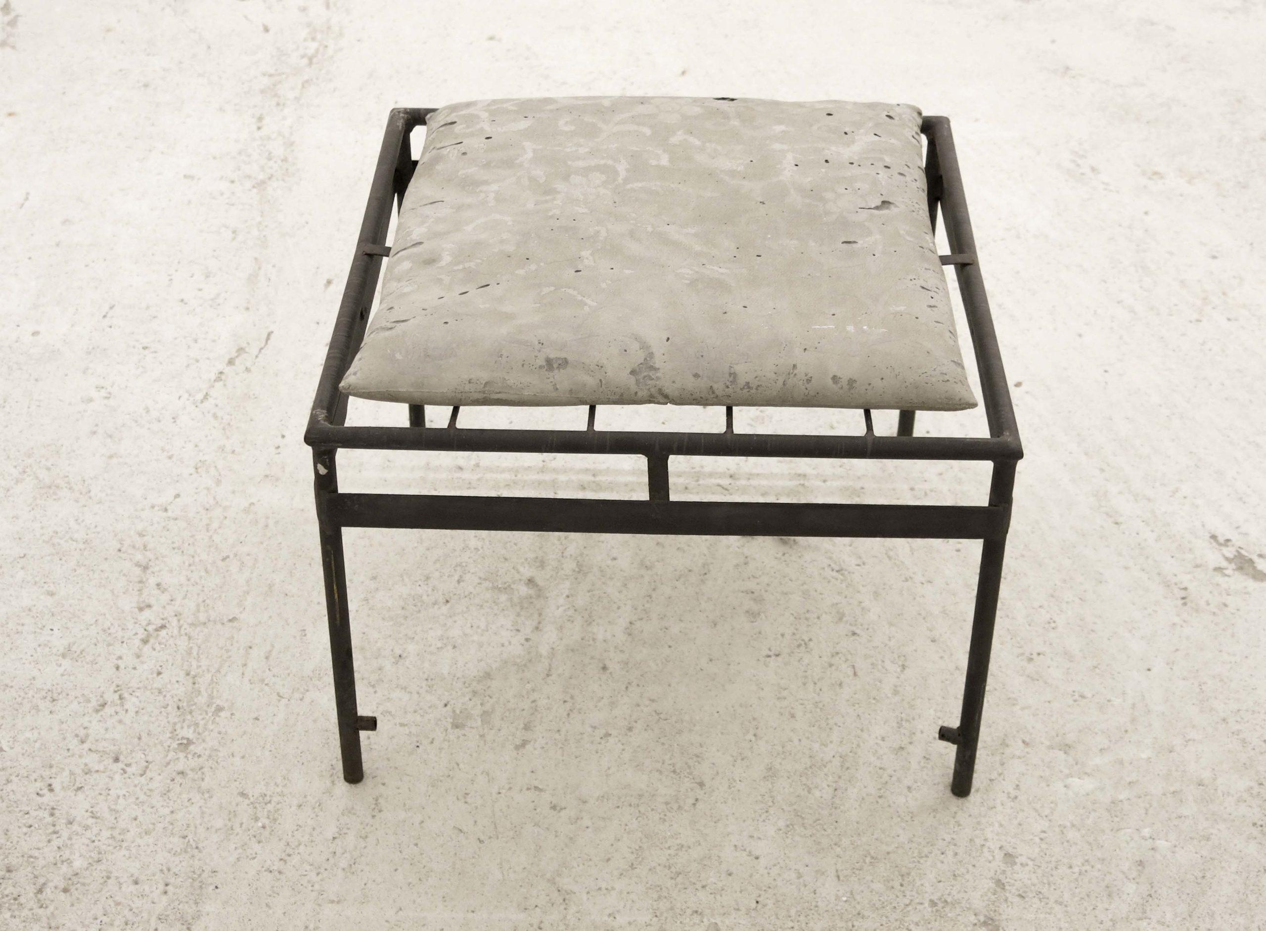 cuscino in cemento con impronte floreali su tavolino in ferro